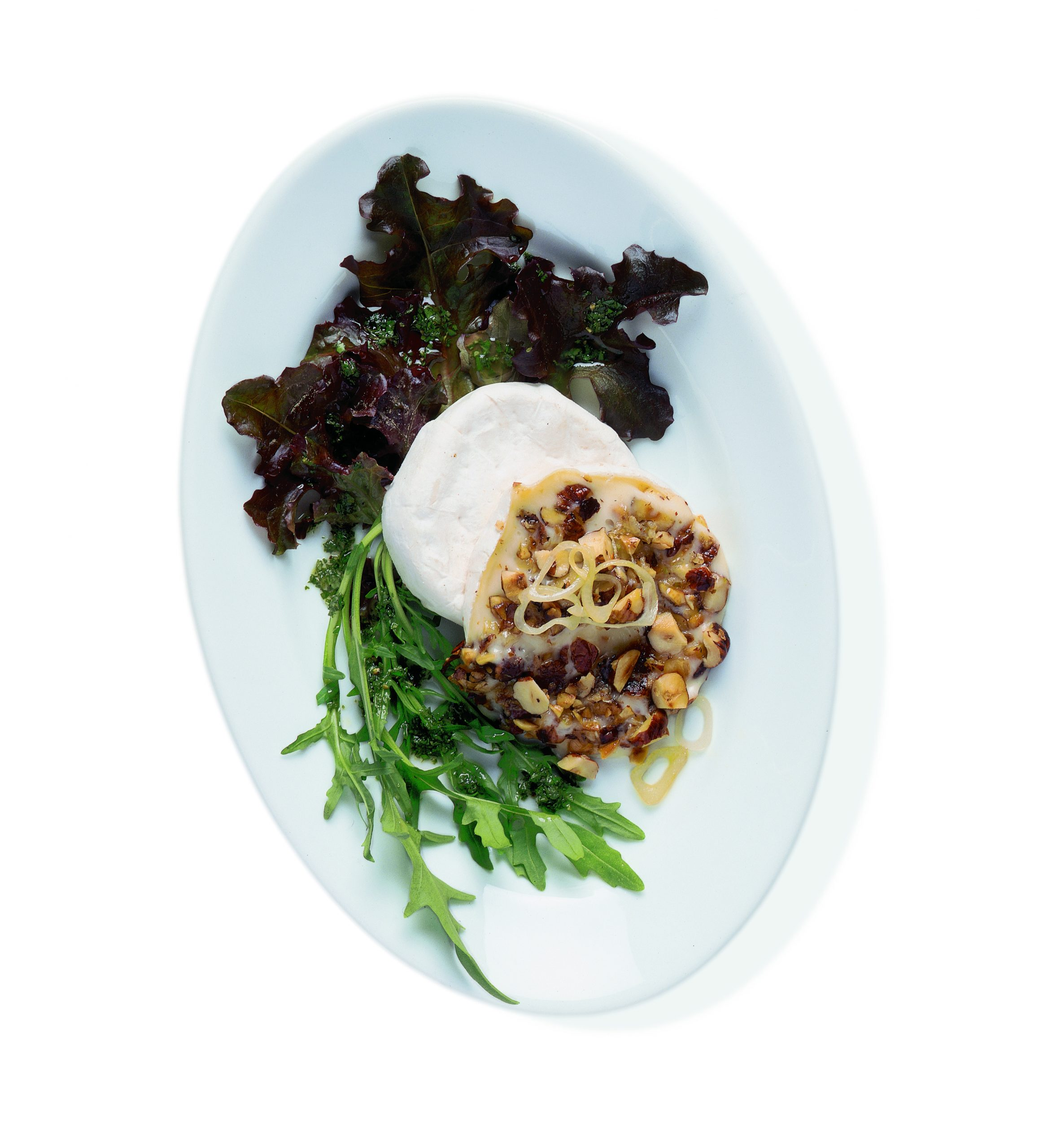 Tomme garnie de noisettes sur lit de salade et vinaigrette aux herbes